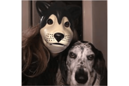 a human wearing a dog mask next to a dog